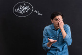 Fotografie confused young man with thought bubble drawing on blackboard