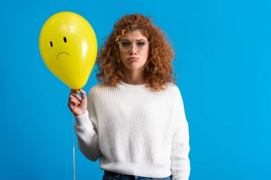 Sad girl holding yellow balloon with upset face, isolated on blue stock vector