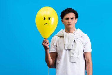 Angry young man holding yellow balloon, isolated on blue stock vector