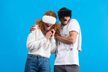 Surprised couple using virtual reality headsets, isolated on blue stock vector