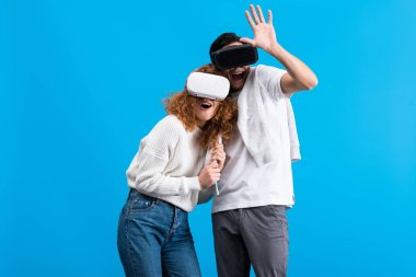 Excited couple using virtual reality headsets, isolated on blue stock vector