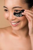 úsměv krásný nahý asijské dívka s černošky hydrogel oko páska izolované na béžové