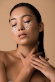 Photo beautiful naked asian girl with rhinestones on face touching neck isolated on beige