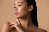 Photo beautiful naked asian girl with rhinestones on face isolated on beige