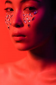 beautiful naked asian girl with rhinestones on face isolated on red