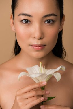 Beautiful naked asian girl holding white lily isolated on beige stock vector