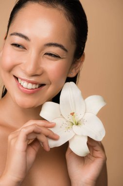 Smiling beautiful naked asian girl holding white lily isolated on beige stock vector