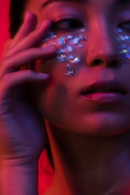 close up view of beautiful asian girl with rhinestones on face, motion blur