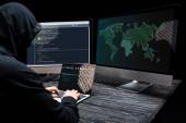 hacker használ laptop kiber biztonsági felirat a képernyőn közelében számítógép monitorok fekete