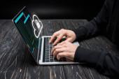 oříznutý pohled na hacker pomocí notebooku s cloudem a visacím zámkem na černé