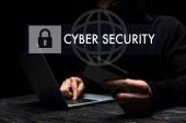 selektivní zaměření hacker v masce pomocí notebooku při držení kreditní karty v blízkosti kybernetické bezpečnosti písmo na černé