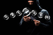 Photo hacker in hood using smartphone and holding credit card near web icons on black