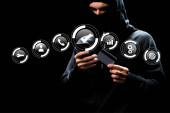 Fotografie Hacker in Kapuze mit Smartphone und Kreditkarte in der Nähe von Web-Symbolen auf schwarz