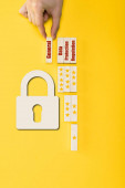 Fotografie top view of man holding wooden block with general lettering near padlock on yellow