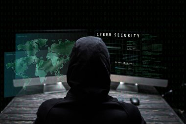 back view of hooded hacker sitting near computer monitors with cyber security lettering on black