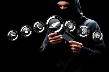 Hacker in hood using smartphone and holding credit card near web icons on black stock vector