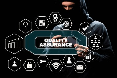 Hacker in hood using smartphone and holding credit card near quality assurance lettering on black stock vector
