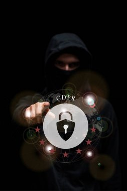 selective focus of hacker in hood pointing with finger at gdpr lettering on black