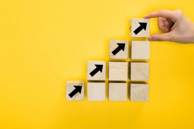 top view of man holding cube with directional arrow isolated on yellow, quality concept