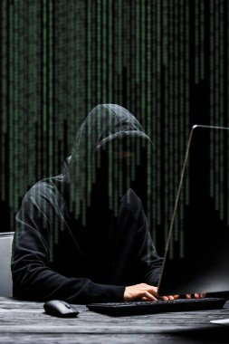 hacker in mask sitting near computer monitor and typing on computer keyboard  near illustration on black