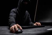 selektivní zaměření počítačové myši v ruce na hacker izolované na černé