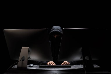 hooded hacker in mask sitting near computer monitors isolated on black