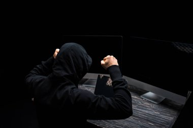 upset hacker with clenched fists near computer monitors with blank screen isolated on black