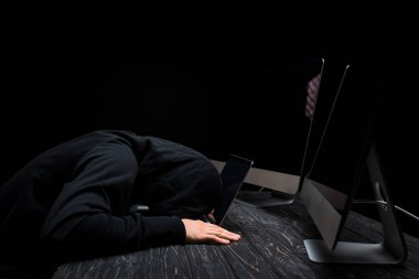 upset hacker lying on laptop near computer monitors with blank screen isolated on black