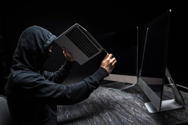 hacker holding laptop near computer monitors with blank screen isolated on black