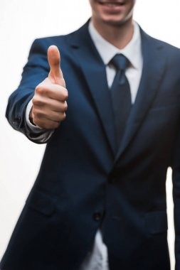 Selective focus of happy businessman in suit showing thumb up isolated on white stock vector