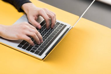 Cropped view of hacker using laptop on yellow desk stock vector