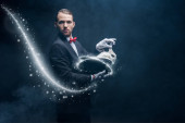 professional magician in suit showing trick with white rabbit in hat, dark room with smoke and glowing illustration