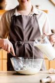 oříznutý pohled šťastné ženy nalévání mléka do misky s moukou
