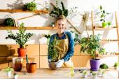 šťastná dívka v zástěře a rukavice s úsměvem v blízkosti zelených rostlin