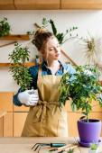 schöne Frau in Schürze hält Blumentöpfe mit Pflanzen