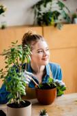 Selektiver Fokus des glücklichen Mädchens in Handschuhen, das eine kleine Schaufel hält, während es Pflanzen im Blumentopf pflanzt