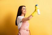 fröhliche Hausfrau in Schürze und Gummihandschuhen, die Lufterfrischer auf gelbem Hintergrund versprühen