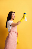 glückliche Hausfrau in Schürze und Gummihandschuhen, die Lufterfrischer auf gelbem Hintergrund versprühen