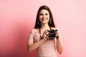 glücklicher Fotograf lächelt, während er die Digitalkamera auf rosa Hintergrund hält