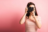 photographer in elegant dress taking photo on digital camera on pink background