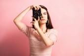 beautiful photographer taking photo on digital camera on pink background