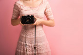 cropped view of photographer in elegant dress holding digital camera on pink background