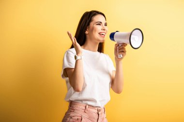 happy girl speaking in megaphone while standing with open arm and looking away on yellow background