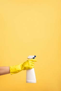 cropped view of female hand in rubber glove with spray bottle isolated on yellow