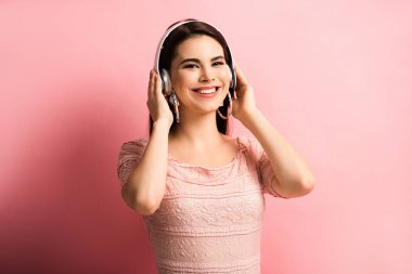 cheerful girl touching wireless headphones while looking at camera on pink background