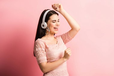 happy girl in wireless headphones dancing and singing on pink background