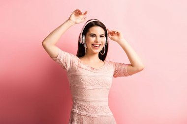 cheerful girl in wireless headphones dancing with open arms on pink background