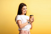 happy attractive girl smiling while holding coffee to go isolated on yellow