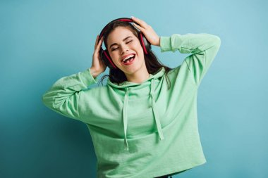 excited girl in wireless headphones singing with closed eyes on blue background