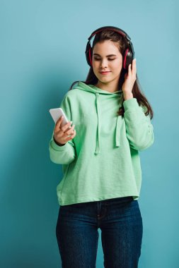 smiling girl in wireless headphones looking at smartphone on blue background